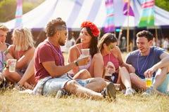 Amis s'asseyant sur l'herbe parlant au festival de musique Photos stock