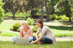Amis s'asseyant sur la pelouse avec un ordinateur portatif Photographie stock libre de droits