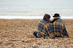 Amis s'asseyant sur la plage Photo stock