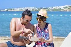 Amis s'asseyant sur la plage, ayant l'amusement avec des comprimés Photo libre de droits