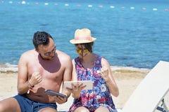 Amis s'asseyant sur la plage, ayant l'amusement avec des comprimés Photos libres de droits