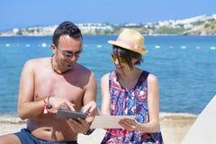 Amis s'asseyant sur la plage, ayant l'amusement avec des comprimés Image libre de droits
