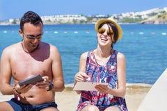 Amis s'asseyant sur la plage, ayant l'amusement avec des comprimés dans les mains Photo stock