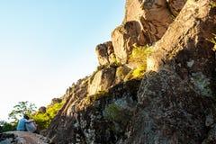Amis s'asseyant sur la roche en canyon, embrassant Images libres de droits