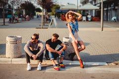 Amis s'asseyant sur la rue et semblant fâchés Photo stock