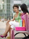 Amis s'asseyant sur le banc avec des sacs à provisions Photo libre de droits