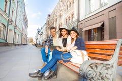 Amis s'asseyant sur le banc tenant ensemble le comprimé Photos libres de droits