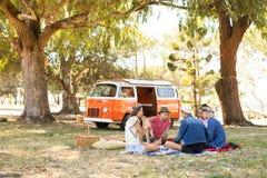Amis s'asseyant sur le champ pendant le pique-nique Images libres de droits