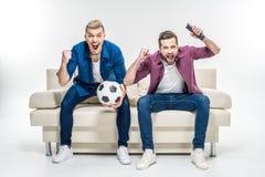 Amis s'asseyant sur le divan avec du ballon de football Photos libres de droits