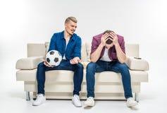 Amis s'asseyant sur le divan avec du ballon de football Image libre de droits