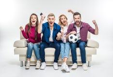Amis s'asseyant sur le divan avec du ballon de football Image stock