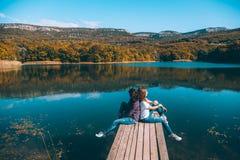 Amis s'asseyant sur le pair par le lac photographie stock