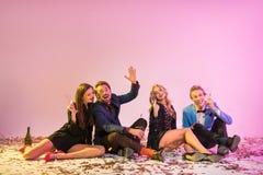 Amis s'asseyant sur le plancher avec des confettis Photos libres de droits