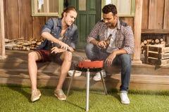 Amis s'asseyant sur le porche avec des bouteilles à bière et et grillant la viande Images libres de droits