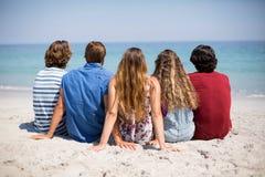 Amis s'asseyant sur le rivage à la plage pendant le jour ensoleillé Photos libres de droits
