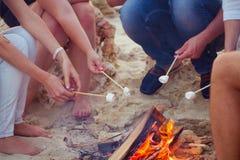 Amis s'asseyant sur le sable à la plage en cercle avec marshmal Photo stock