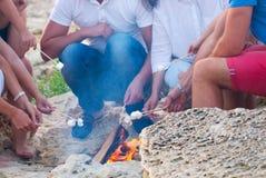 Amis s'asseyant sur le sable à la plage en cercle avec marshmal Images stock