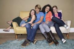 Amis s'asseyant sur le sofa Image stock