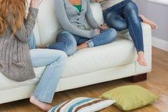 Amis s'asseyant sur le sofa avec le coussin sur le plancher à la maison Photos libres de droits