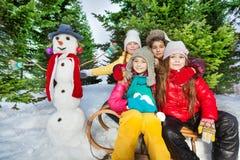 Amis s'asseyant sur le traîneau près du bonhomme de neige mignon Image stock