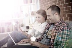 Amis s'asseyant sur un café potable de sofa et surfant sur le Web Photographie stock