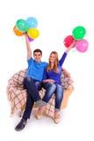 Amis s'asseyant sur un sofa avec des ballons Photos stock