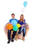 Amis s'asseyant sur un sofa avec des ballons d'isolement Images stock
