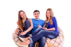amis s'asseyant sur un sofa et une soude potable Images stock