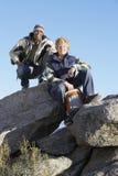 Amis s'asseyant sur une roche Photographie stock libre de droits