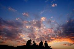 Amis s'asseyant sur une roche pendant la silhouette de coucher du soleil image libre de droits