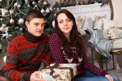 Amis s'asseyants avec le cadeau près de l'arbre de Noël Image stock