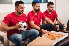 Amis s'enracinant pour leur équipe de football Photographie stock libre de droits