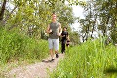 Amis s'exerçant dans la piste de forêt Photos libres de droits