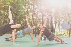 Amis s'exerçant ensemble en parc Photographie stock libre de droits
