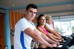 Amis s'exerçant sur un tapis roulant au gymnase moderne lumineux Photo stock