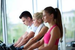 Amis s'exerçant sur un tapis roulant au gymnase moderne lumineux Images stock