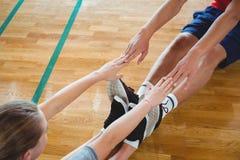 Amis s'exerçant tout en se reposant sur le plancher en bois dur Photographie stock