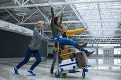 Amis satisfaits ayant l'amusement avec le chariot de bagages Photos libres de droits
