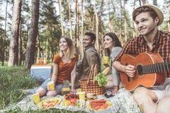Amis satisfaits détendant avec la musique en nature Photos stock