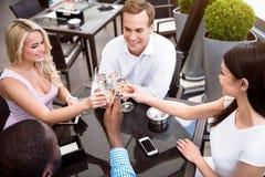 Amis satisfaits gais s'asseyant dans le café Photos stock