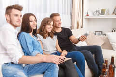 Amis satisfaits regardant la TV Photos libres de droits