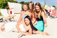 Amis se bronzant dans la barre de plage sur le sable Images stock
