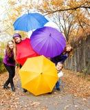 Amis se cachant derrière des parapluies Photographie stock libre de droits