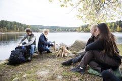 Amis se préparant à camper sur au bord du lac Photographie stock libre de droits