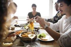 Amis se réunissant ayant la nourriture italienne ensemble Image stock