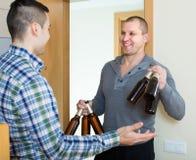 Amis se réunissant pour boire de la bière à la maison Photos stock