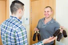 Amis se réunissant pour boire de la bière à la maison Image libre de droits