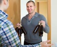 Amis se réunissant pour boire de la bière à la maison Photos libres de droits