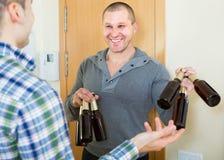 Amis se réunissant pour boire de la bière à la maison Photographie stock libre de droits