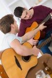 Amis se reposant à la maison et jouant la guitare Photos stock